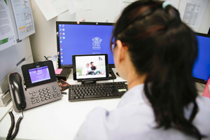 Health professional in telehealth consultation with family